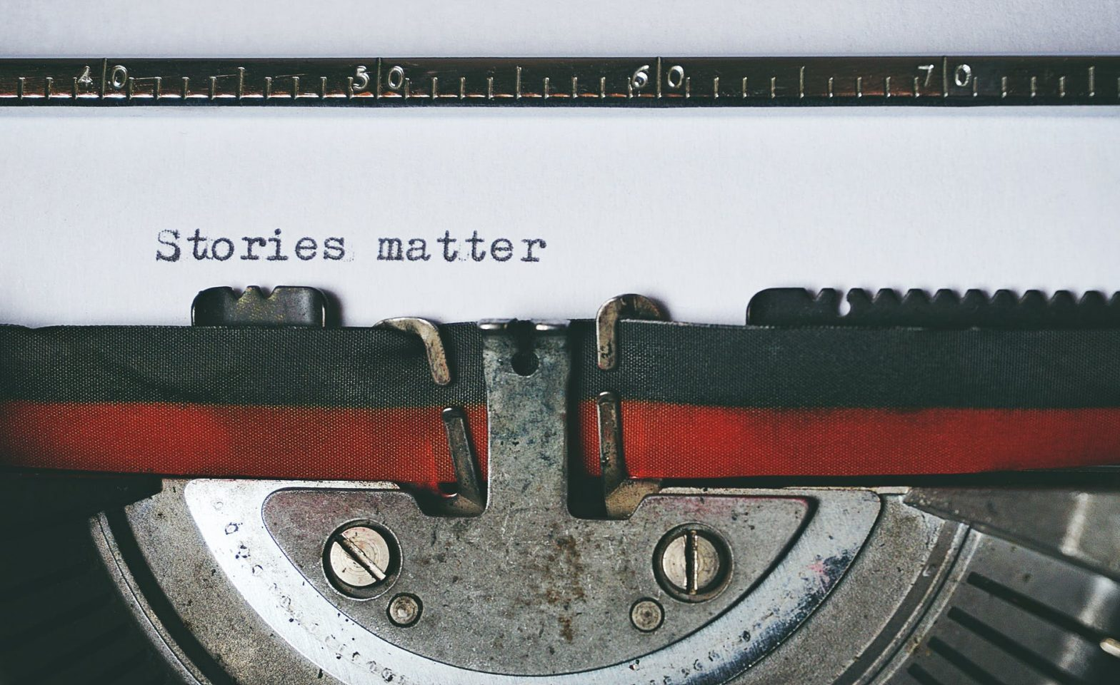 "black and red typewriter, with ""Stories matter"" typed on the paper."